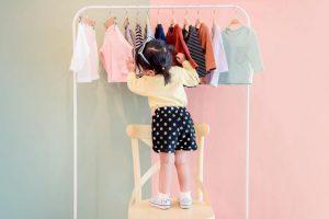 criança escolhendo roupas infantis